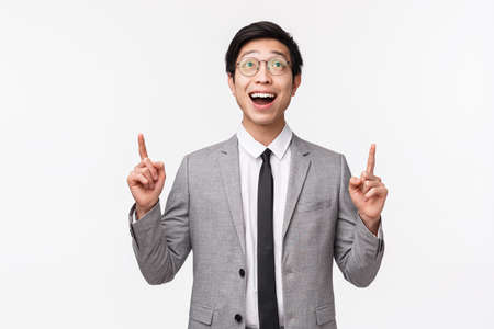 Waist-up portrait of dreamy and happy smiling asian male office manager, entrepreneur seeing something breathtaking, look and pointing up amazed with cool product promo, white background