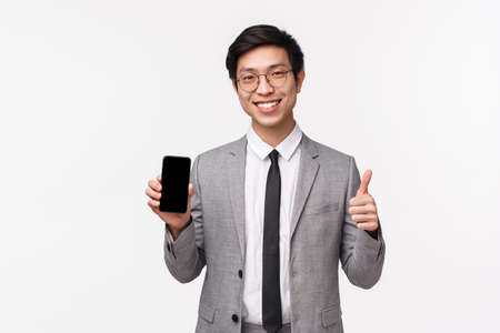Waist-up portrait of satisfied good-looking asian young man in grey suit, show mobile phone display and thumbs-up, approval cool new application, recommend buy subscription, white background