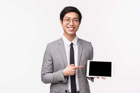 Waist-up portrait of pleasant confident asian office manager, wearing glasses and suit, holding digital tablet and pointing at screen to introduce his project, show presentation to team, smiling