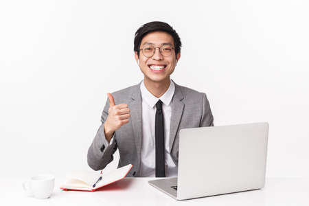 Portrait of happy and cheerful young asian male entrepreneur, office manager working on project, sitting table with notebook and laptop, answer calls using wireless earphones show thumbs-up