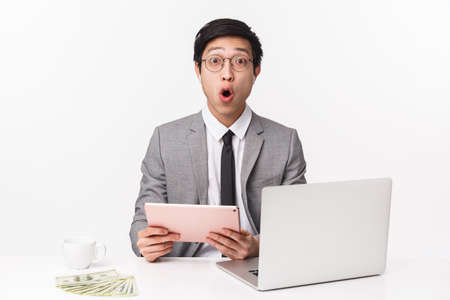 Waist-up portrait of successful rich asian businessman got bit sum of money, sitting at desk with thousands dollars, laptop and cup coffee, react to wonderful news at internet, use digital tablet