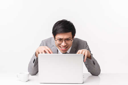 Portrait of distressed, pressured and stressed young asian office worker work hard over project, hurry up typing fast to meet deadline making intense grimace as bending over computer, input info