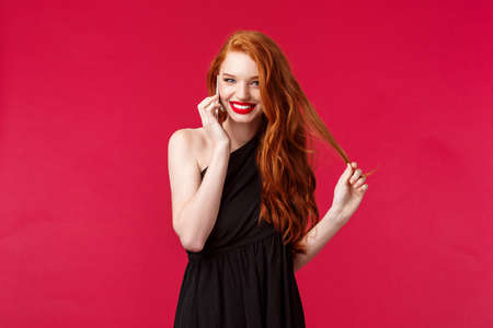 Portrait of coquettish flirty feminine redhead woman in black dress giggle while talking on phone with bae, hold smartphone near ear calling someone flirting and smiling, wear black dress Reklamní fotografie