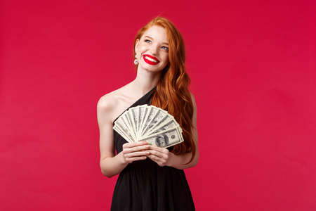 Luxury, beauty and money concept. Portrait of lucky and carefree rich attractive redhead woman in stylish evening dress, laughing happy looking up thinking, holding cash dollars, red background