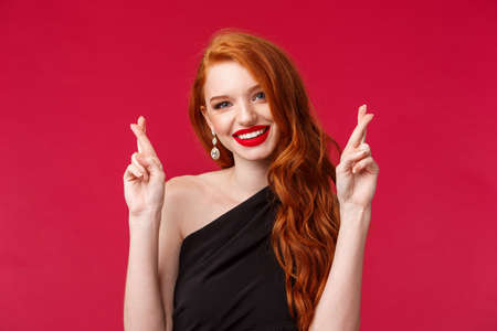 Close-up portrait of optimistic gorgeous redhead woman, praying for dream come true, cross fingers and smiling camera, assure she will win, determined receive prize, stand red background