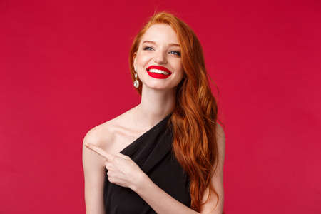 Close-up portrait of delighted pretty romantic redhead woman in red lipstick, black dress, contemplate something beautiful, pointing and looking left with happy silly smile, red background