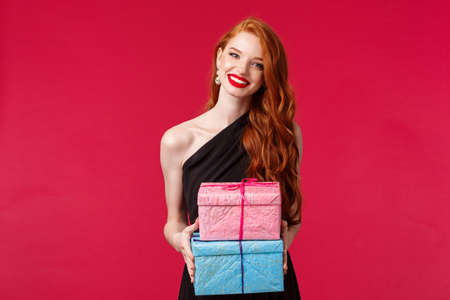 Celebration, holidays and women concept. Charming redhead female in black evening dress, red lipstick, give presents to birthday girl, party owner, holding two gifts and smiling cheerful