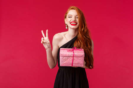 Celebration, holidays and women concept. Happy gorgeous young redhead female with long red hair, lipstick, wear black evening dress, have birthday party, laughing and smiling, hold gift