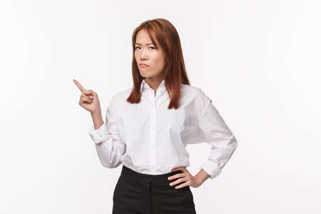 Portrait of serious-looking doubtful and skeptical young asian woman pointing finger left and looking camera with disbelief and pissed-off expression, being suspicious, white background Stockfoto