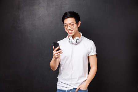 Technology, gadgets and people concept. Happy smiling asian male student standing casually in t-shirt, wearing headphones over neck, look at smartphone with pleased grin, messaging