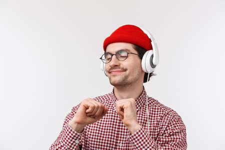 Just vibing. Happy carefree young hipster guy with moustache in glasses and red beanie dancing joyfully, listening to favorite song in headphones with pleased relaxed face, standing white background 写真素材 - 143282711