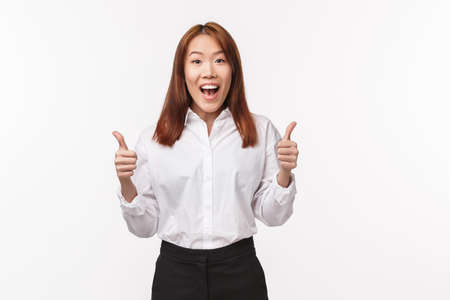 Good job, nice work team. Cheerful enthusiastic female entrepreneur, successful asian woman show thumbs-up and smiling with approval, agree give positive reply, recommend product