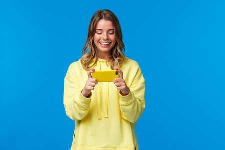 Time to relax on lunch break. Carefree good-looking hipster girl in yellow hoodie using mobile phone to play, holding smartphone horizontal position and smiling as passing easy game level