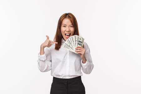 Portrait of excited and cheerful young asian woman in shirt and skirt, pointing at cash and looking daring camera, earn lots money, telling secret how to earn, suggest career, white background