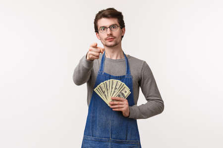 Small business, finance and career concept. Portrait of serious-looking young determined guy telling you secret how to earn money, become rich on your enterprise, hold cash and point camera