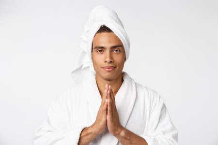 Calm spiritual handsome African guy praying. Serious peaceful young man with joining hands meditating. Belief concept