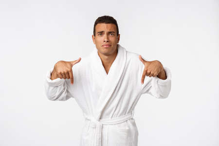 African American guy wearing a bathrobe pointing finger with surprise and happy emotion. Isolated over white background