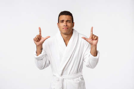 African American guy wearing a bathrobe pointing finger with surprise and happy emotion. Isolated over whtie background Reklamní fotografie