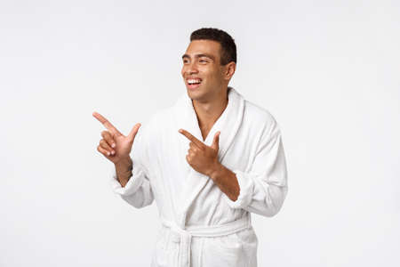 African american guy wearing a bathrobe pointing finger with surprise and happy emotion. Isolated over white background.