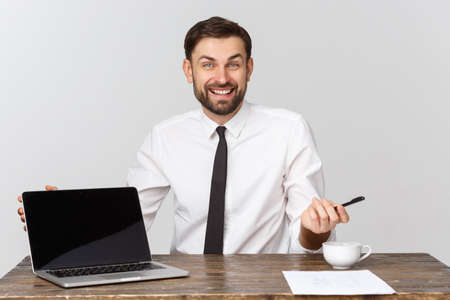 businessman sitting at desk point finger at isolated white laptop screen with empty copy space, handsome young business man.