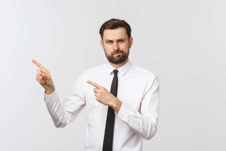 Bearded serious businessman pointing finger at you. Isolated on grey studio background