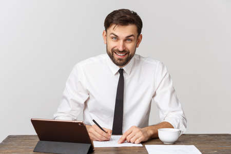 A view of a busy businessman signing a document in the office against white background 写真素材
