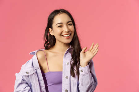 Close-up portrait of happy good-looking asian girl saying hi, waving hand casually, informal greeting sign, laughing and smiling friendly, welcome friend, greet hello, stand pink background 版權商用圖片