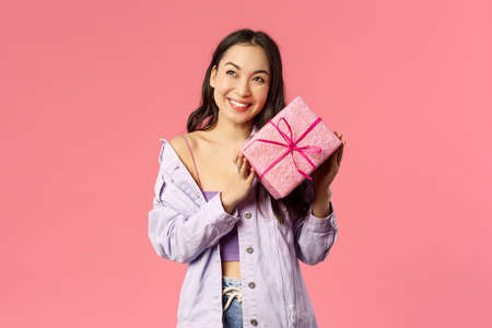 Curious whats inside. Portrait of cute silly asian girl shaking box with gift to guess what is it, smiling amused, leaning to present with ear trying hear movement, standing pink background
