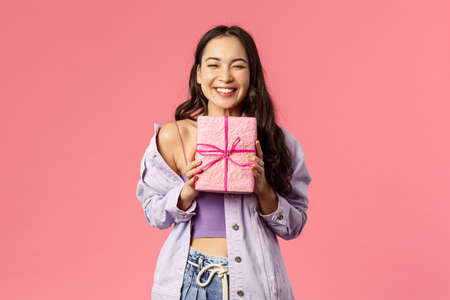 Portrait of cheerful, happy asian girl receive gift, smiling excited, holding wrapped present and cant hide happiness, celebrating birthday, being invited to b-day party, pink background