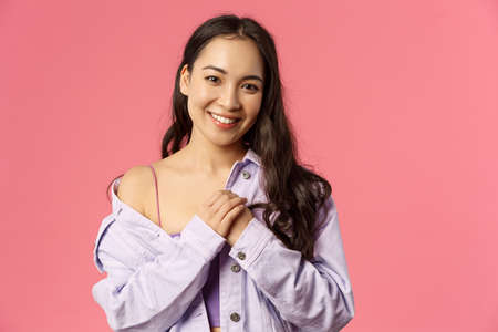 Close-up portrait of tender, romantic asian girl keep loving dearest memories in her heart, press hands to chest, smiling and looking thankful camera, standing pink background