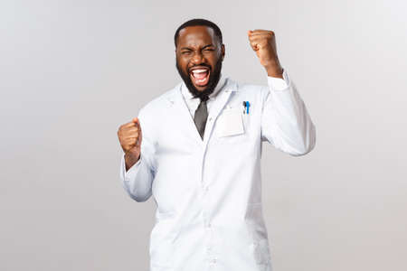 Yes we did it, no more covid19. Triumphing and happy, excited african-american doctor finally found coronavirus vaccine, treated last patient, raise hands up scream yes, celebrating success
