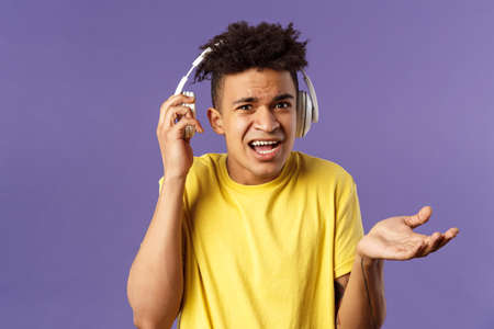 What do you want, I am in headphones. Portrait of confused annoyed young man shrugging, take-off earphone to hear what person asked while he was listening music, purple background