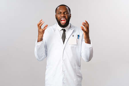 Angry, hateful african-american male doctor pissed-off people dont follow prescriptions, walking outdoors during covid19 quarantine, panemic outbreak, shaking hands and scream outraged Stock Photo