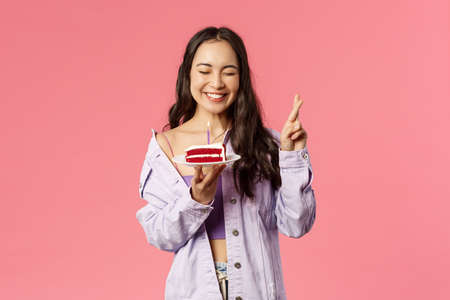 Celebration, holidays and people concept. Portrait of cheerful carefree, pretty asian girl cross fingers, close eyes and smiling joyfully while making wish before blowing candle on birthday cake