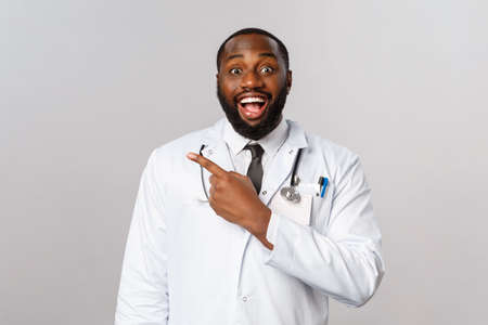 Covid19, hospital check-up and healthcare concept. Excited, smiling african-american doctor, hear fantastic news, pointing fingers upper left corner, laboratory had positive result testing vaccine