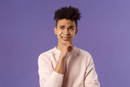 Close-up portrait of indecisive, puzzled young man facing difficult choice, look up thoughtful, touch chin and grimacing while thinking, making-up idea or decision, purple background