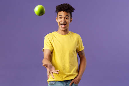 Holidays, vitamins and vacation concept. Portrait of handsome upbeat young male student asking friend something eat, catching apple and smiling happy, standing purple background