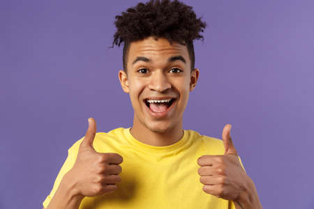 Close-up portrait of enthusiastic, lively hipster guy with afro haircut agree with something, show thumbs-up smiling with joy, recommend good product, like and approve plan, purple background