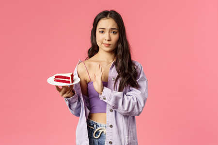 Portrait of skeptical young asian stylish slim girl refusing eat cake, smirk show top sign to dessert lying on plate, rejecting try it, disappointed with bad taste, stand pink background