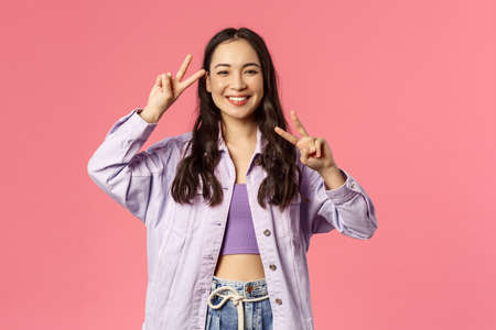 Kawaii asian girl sending good positive vibes, enjoying bright sunny weekend, having fun, partying and brighten up your day with beaming happy smile show peace gesture, pink background