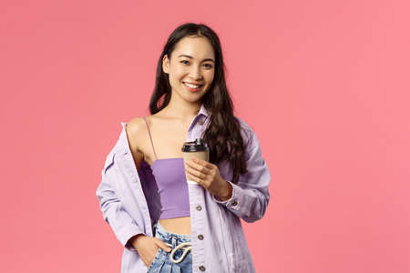 Lifestyle, modern people and beauty concept. Sassy good-looking asian girl chilling with friends at favorite cafe, grab take-away beverage, drinking coffee and smiling camera, pink background 版權商用圖片