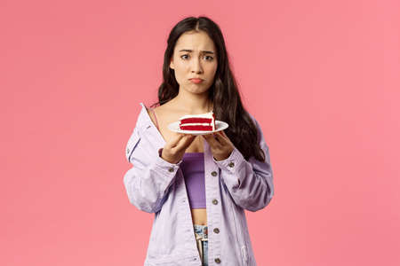 Portrait of gloomy sad cute asian girl just being dumped trying eat-out her sadness, holding piece cake, pouting and frowning upset, have uneasy feelings, grieving, pink background