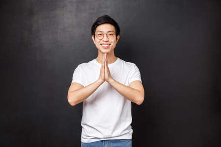 Handsome young asian hipster guy in white t-shirt, glasses, hold hands in namaste, pray gesture smiling grateful, thanking for help, pleading or making wish, standing black background