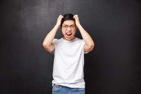 Angry and pissed-off bothered young asian guy losing temper, screaming outraged, ripping hair out of head and grimacing aggressive, feel distressed and tensed, hateful expression