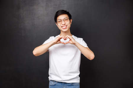 Cute romantic asian man in white t-shirt and glasses tilt head looking at something lovely, express sympathy confess love, show heart sign at camera, standing black background