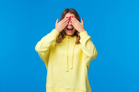 Girl waiting for friends tell her open eyes as shut it with hands and count ten during b-day party, girlfriend bring surprise gift, smiling with excitement, playing peekaboo, stand blue background