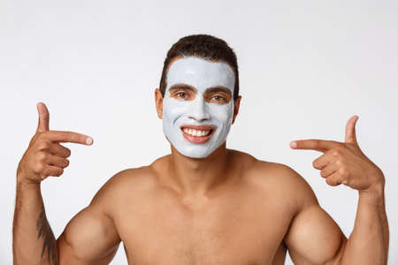 Photo of shirtless african american man smiling and applying face cream isolated over white background