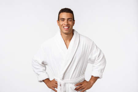 African American guy wearing a bathrobe with happy emotion. Isolated over whtie background.