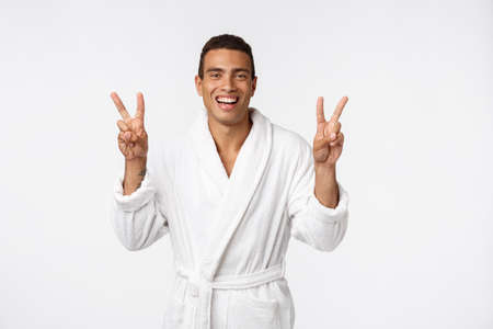 Closeup portrait happy, excited, successful young man giving peace, victory or two sign, isolated white background. 版權商用圖片