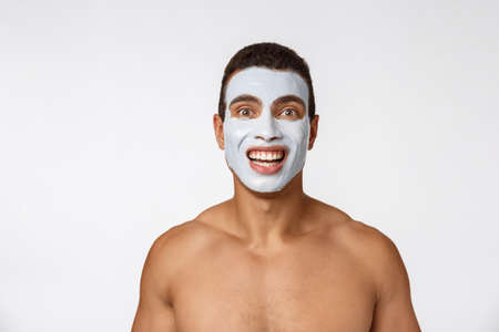 Picture of cheerful nice young african guy smiling on camera. Portrait of man with cream mask on cheeks. Beauty routine